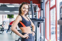 Young sportive woman standing with arms akimbo. At gym stock photo