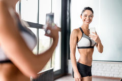 Young Sportive Woman Taking Mirror Selfie in Gym. Portrait of proud muscular  woman smiling boasting her fit figure and slim waist taking selfie in gym mirror Royalty Free Stock Images