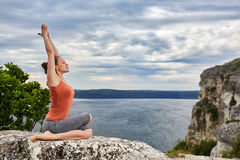 Young sportive woman training yoga asanas on rock above beautiful river. Royalty Free Stock Photos