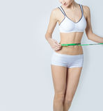 Young sports a beautiful slim woman measuring perfect shape nice hips, the concept of a healthy lifestyle on a white background royalty free stock images