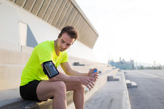 Young sports build man sitting on concrete stairs while taking break after fitness training outdoors Royalty Free Stock Photos