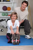 Young sports coach with senior woman. Senior woman stretching with sports coach Stock Photography