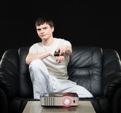 Young sports fan watching football on a sofa Stock Photography