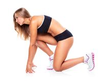 Young sports girl does exercises on a white Stock Image