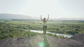 Young sports girl standing on top of the high cliff above the river at beautiful golden sunset, raising her hands up in