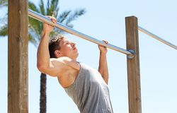 Young sports guy pull up exercise routine. Outdoor Royalty Free Stock Photography