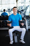 Young sports guy sitting on bench with a dumbbell Royalty Free Stock Image