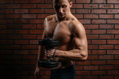 Young sports guy trains the biceps. In the gym Stock Photo