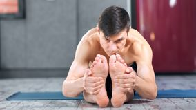 Young sports man doing pilates reaching bare foot by hands showing stretching full shot. Professional focused yogi male practicing yoga exercise indoor front stock video footage