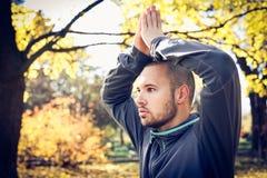 Young sports man doing yoga. Autumn season. Stock Images