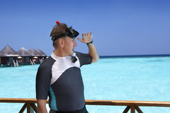 Young sports man with flippers, mask and tube on sundeck of a house over the sea. Maldives Stock Photos