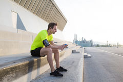 Young sports man holding bottle of water while taking break after an active run outdoors in early morning Stock Photo