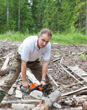 The young sports man in a light shirt green trousers and rubber boots works in the wood with a chain saw Stock Image