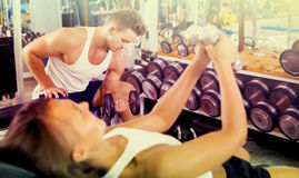 Young sports man making biceps curls in gym. Young sports men making biceps curls using heavy dumbbells in gym Stock Photos