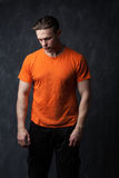 Young sports man in an orange shirt hung his head royalty free stock images