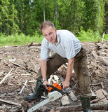The young sports man in rubber boots works in the wood with a chain saw Royalty Free Stock Images