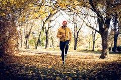 Young sports man run trough public park. Stock Photos