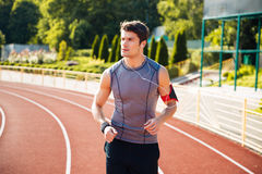 Young sports man running down stadium track with earphones Stock Photos