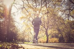 Young sports man running trough city park. Stock Photo