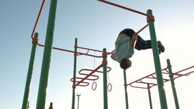Young sports man with strong body training in active sports making pull up on the horizontal fitness bar outdoors.