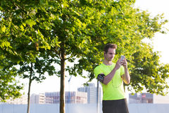 Young sports man uses mobile phone to choose songs in music player list while preparing for his early morning run in urban park Royalty Free Stock Image