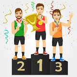 Young sports men holding a cup and medals Royalty Free Stock Image
