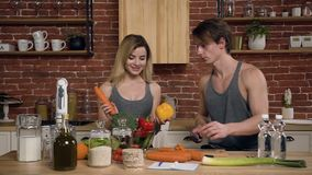 Young sports people are talking and smiling while cooking healthy food. A young man cutting carrot for prepare salad stock footage