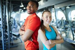 Sports trainers. Young sports professionals or athletes in activewear standing back to back in modern fitness center stock photography