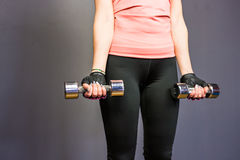 Young sports sexy fitness woman with dumbbells posing on wall background. Stock Photo