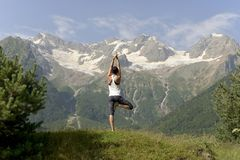 Young sports woman doing yoga in the summer on the background of snowy mountains. stock photography