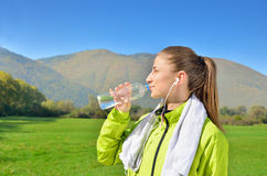 Young sports woman enjoys fitness and bright sunshine. Listens to music Royalty Free Stock Photos