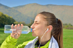Young sports woman enjoys fitness and bright sunshine. Listens to music Royalty Free Stock Images
