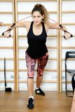 Young sports woman in gym using equipment trx Stock Photos
