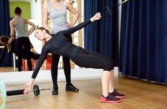 Young sports woman in gym using equipment trx Stock Images