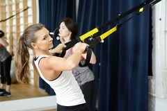 Young sports woman in gym using equipment trx Royalty Free Stock Image