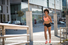 Young sports woman jogging on city road in broad daylight Royalty Free Stock Photography