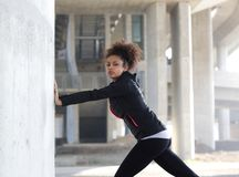 Young sports woman pushing against wall Royalty Free Stock Photo