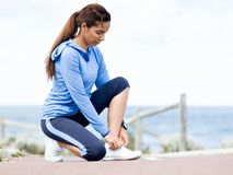Woman runner tying shoelace at the seaside Stock Images