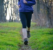 Young Sports Woman Running on the Forest Trail in the Morning Stock Photo