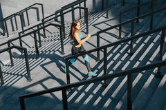 Young sports woman running up on stone stairs. stock photography