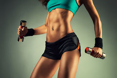 Young sports woman. Young sports sexy fitness woman body with dumbbells posing on wall background Stock Images