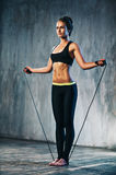 Young sports woman. Young sports sexy fitness woman with skipping rope on wall background Stock Photos