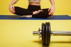 Young sports woman sits on the floor in pose of lotus near the dumbbells, at the gym. yellow background Royalty Free Stock Images