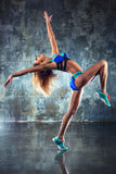 Young sports woman. Young slim sports woman stretching and dancing on wall background Royalty Free Stock Photography