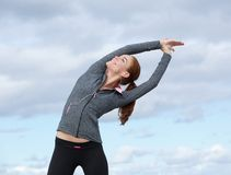 Young sports woman smiling and stretching outdoors Stock Photos