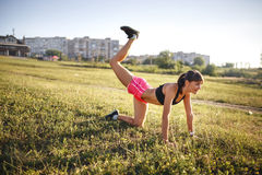 Young sports woman stretching and preparing to run. Royalty Free Stock Photos