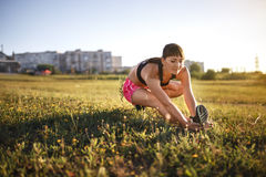 Young sports woman stretching and preparing to run. Royalty Free Stock Photography