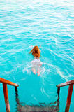 Young sports woman swims from steps of villa Stock Photos