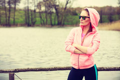 Young sports woman taking break after a run. Sport and lifestyle concept. Young sports woman female jogger taking a break from running workout, relaxing on pier Stock Photo