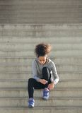 Young sports woman tying shoelaces on steps Royalty Free Stock Images